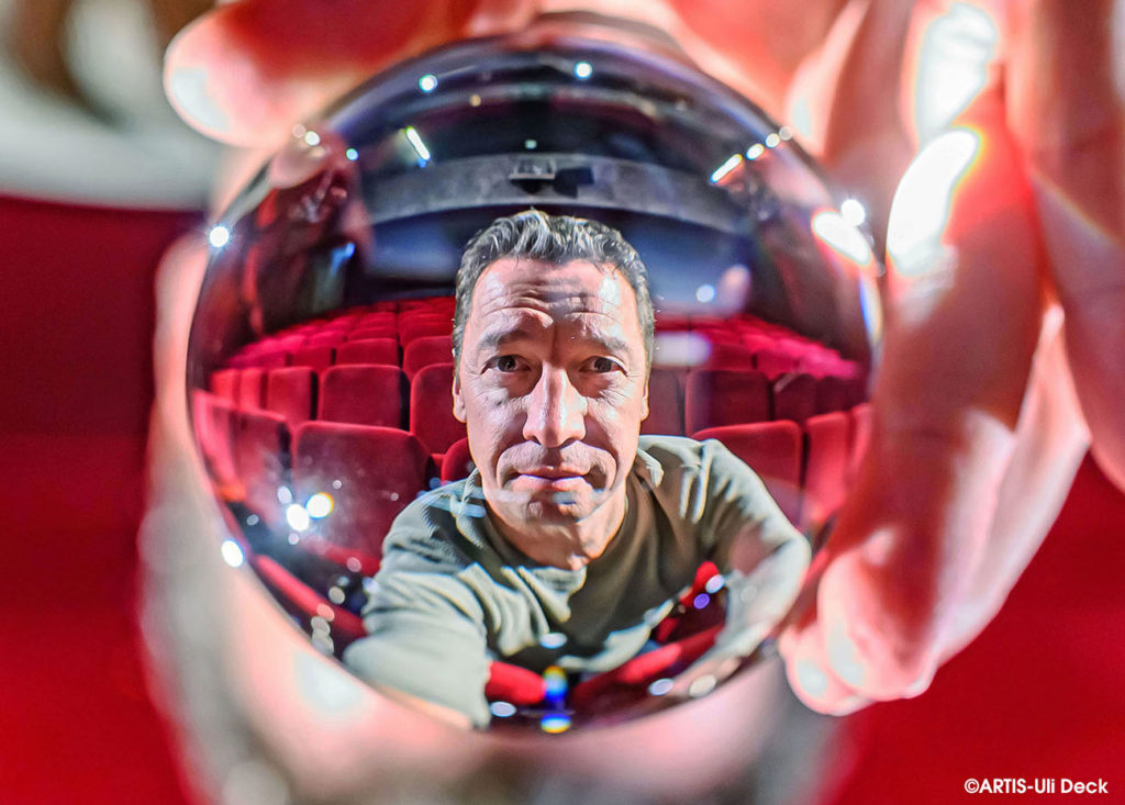 Kulturportrait in Zeiten von Corona -  Bernd Gnann, Geschäftsführer des Kammertheater Karlsruhe, sitzt im Zuschauerraum und blickt durch eine Glaskugel.