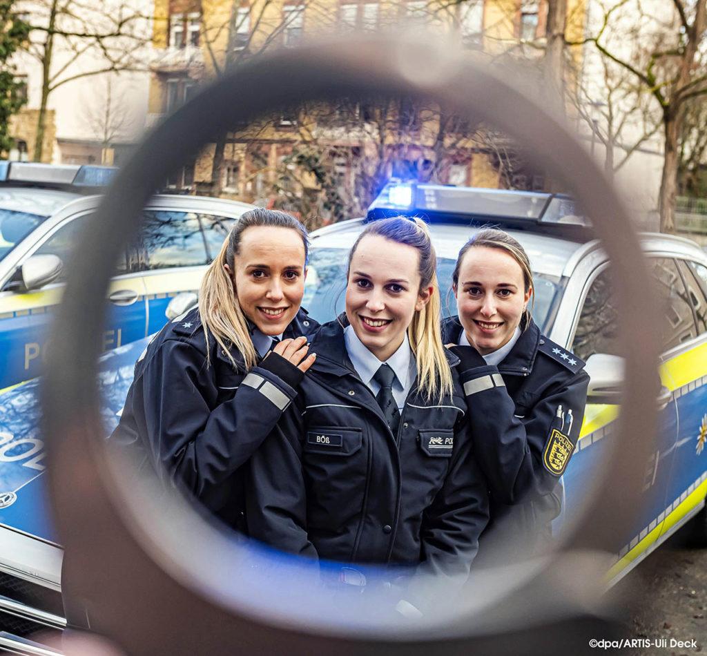 Die eineiigen Drillinge, Vanessa, Lara und Samira Böß, die alle drei bei der Polizei arbeiten, fotografiert durch eine Handschliesse beim Polizeipräsidium Karlsruhe.